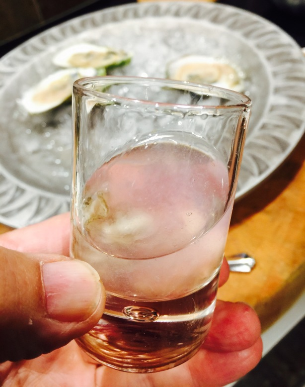 An oyster shooter with pickled red onion shaved ice. Bottoms up!